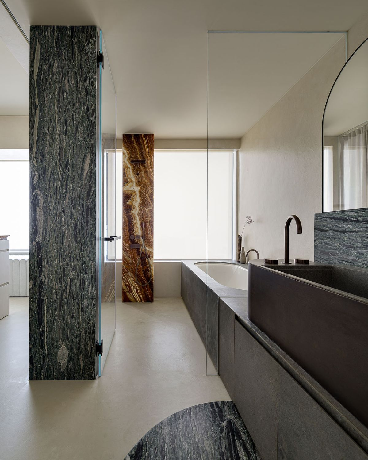 The bathroom features eye-catching marble columns which hide the utilities