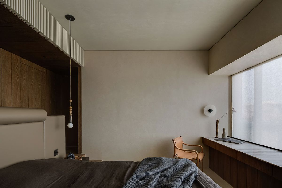 The bedroom is modest in size and has a large window with a stylish and minimalist unit framing it below