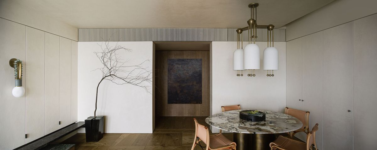 The dining area is positioned in one of the corners and features stylish brass accents and a marble top table