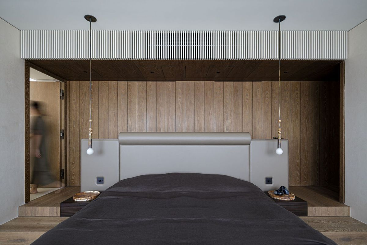 The bed area is symmetrical, featuring matching platforms on either side as well as two low-hanging pendant lamps
