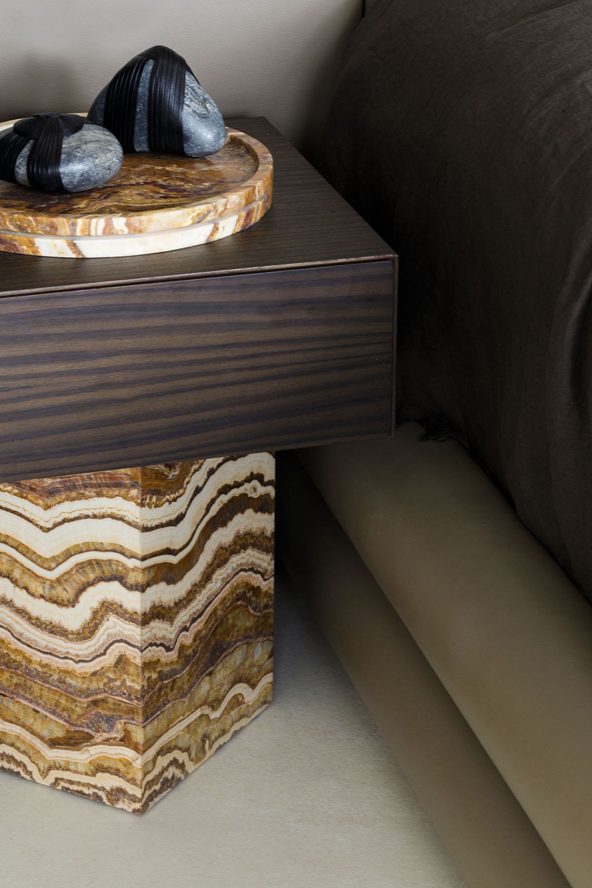 Custom nightstands made of wood and marble establish a harmonious connection between the bedroom and the bathroom's design