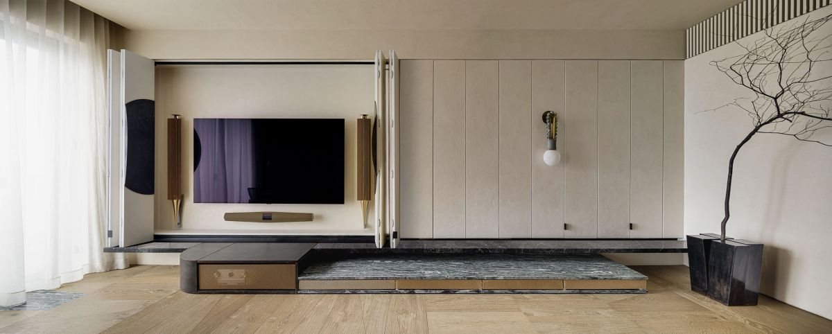 The TV is hidden behind the folding panels on the left side of the wall to avoid it becoming an unnecessary distraction
