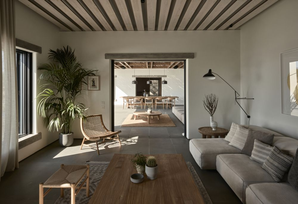 The living area has large windows, smooth white walls and is decorated by earthy color tones