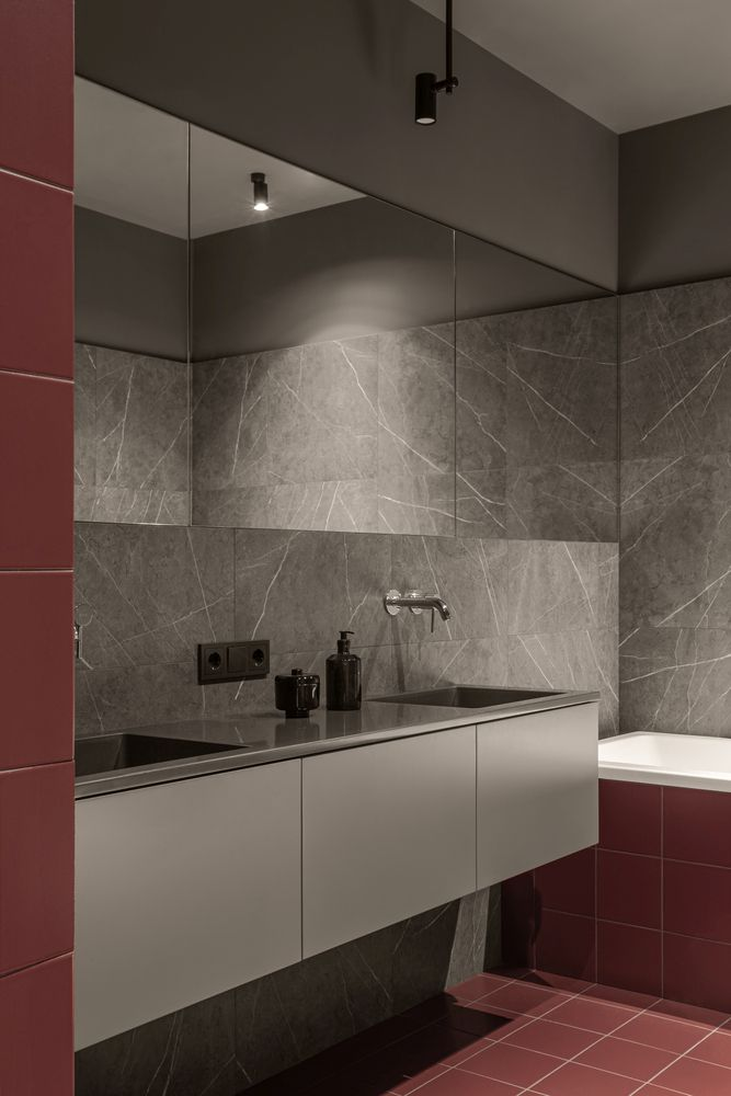 The bathroom is decorated with warm shades of gray and a muted red nuance