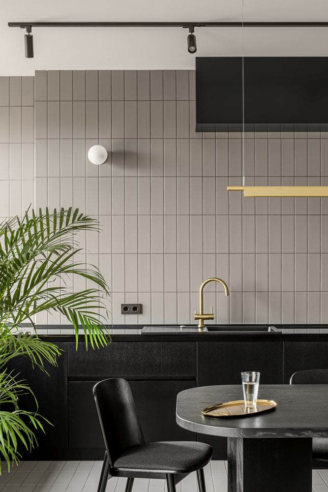 The gray and beige tiles on the kitchen floor and wall are very similar which adds continuity to the decor