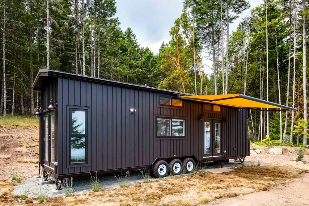 The roll-out awning which marks the entrance adds a dash of color to the exterior of this tiny house