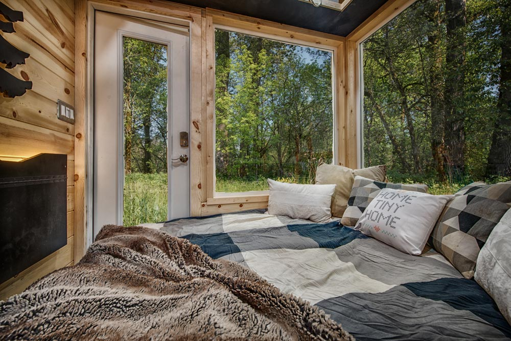 The picture windows fill this tiny home with natural light and bring in the beautiful scenery