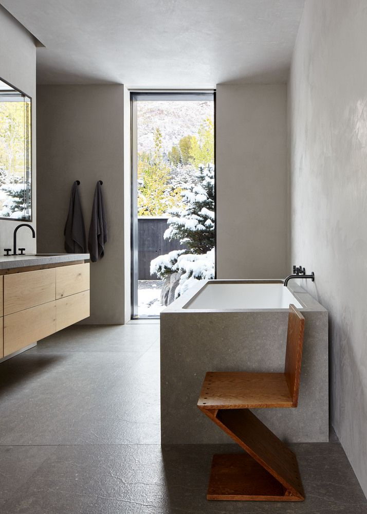 The en-suite is decorated with neutral colors and materials and the focal point here in a tall and narrow window