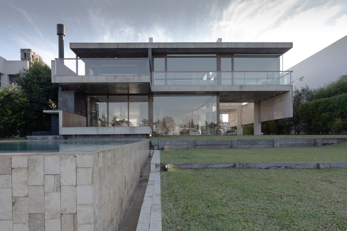 The house sits on a site by the lake, with a gentle slope and uneven terrain