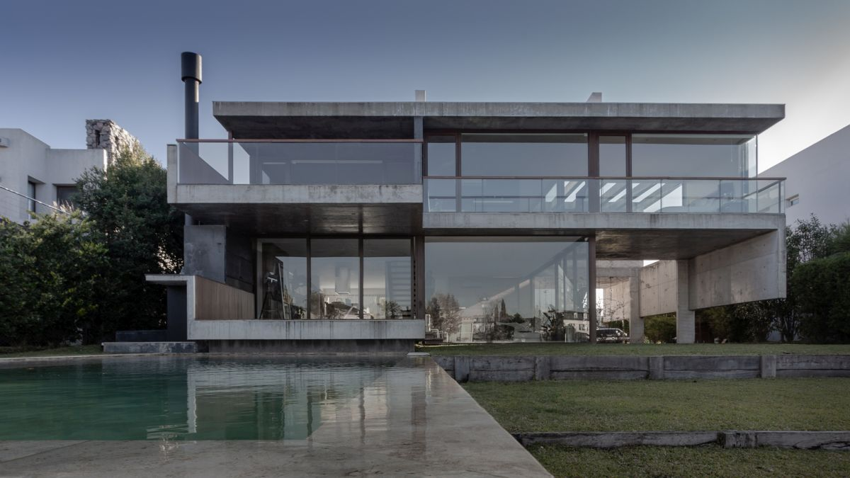 The combination of exposed concrete and glass gives the house a modern-industrial appearance