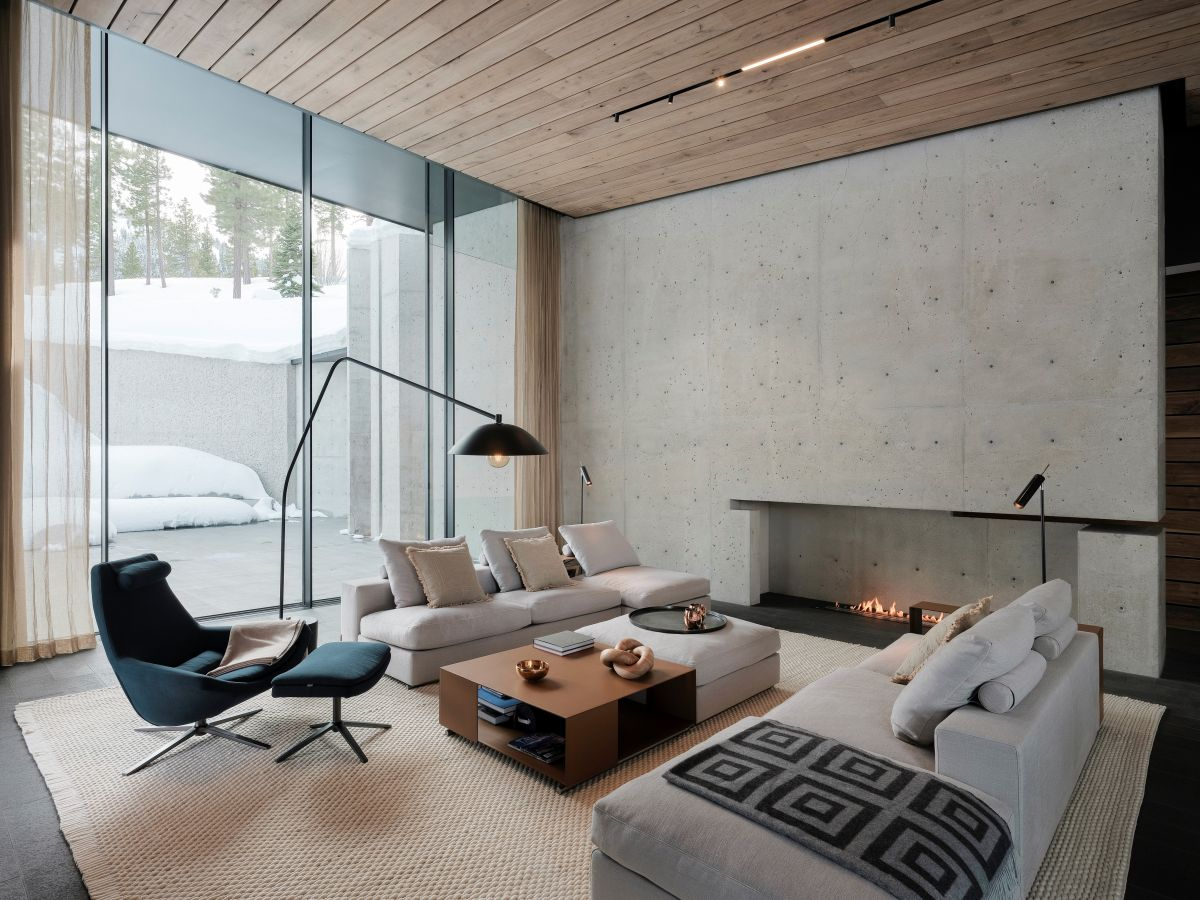 A minimalist and modern fireplace brings warmth to the living room and a large area rug creates a cozy outline