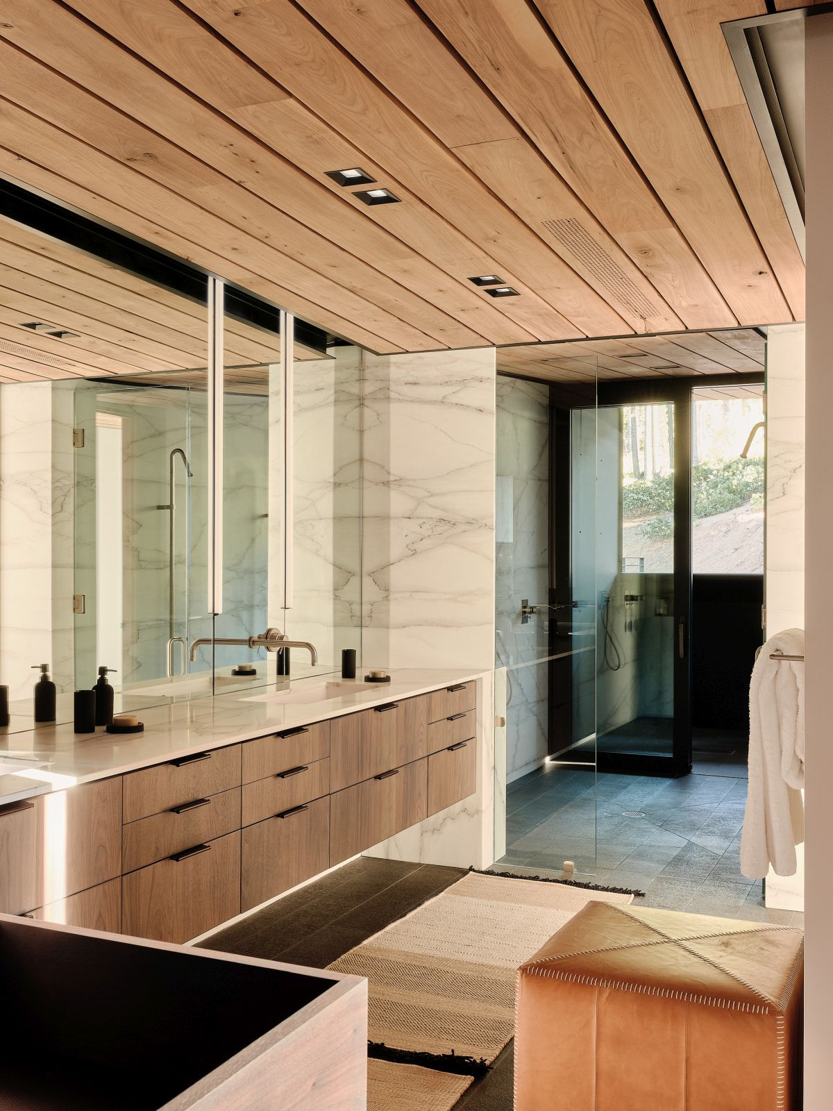 A combination of wood, marble and glass turns the bathroom into a soothing and welcoming space
