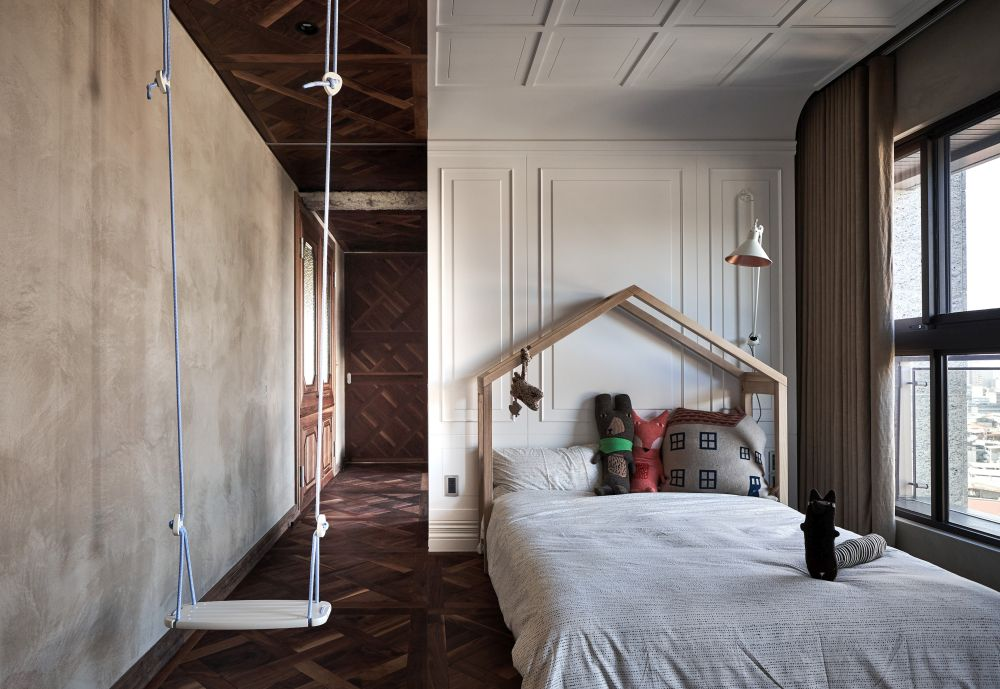 A swing hanging from the ceiling and a bed frame shaped like a house make this bedroom look super cute