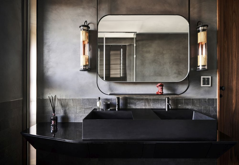The black double sink is super sleek and minimalist and its straight lines are toned down by the soft curves of the mirror