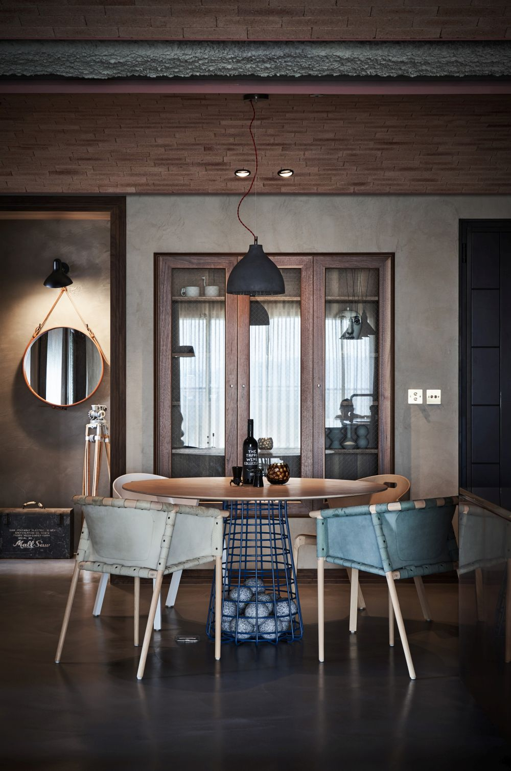 The dining area is small and cozy, centered around a round table next to a display cabinet with glass door fronts