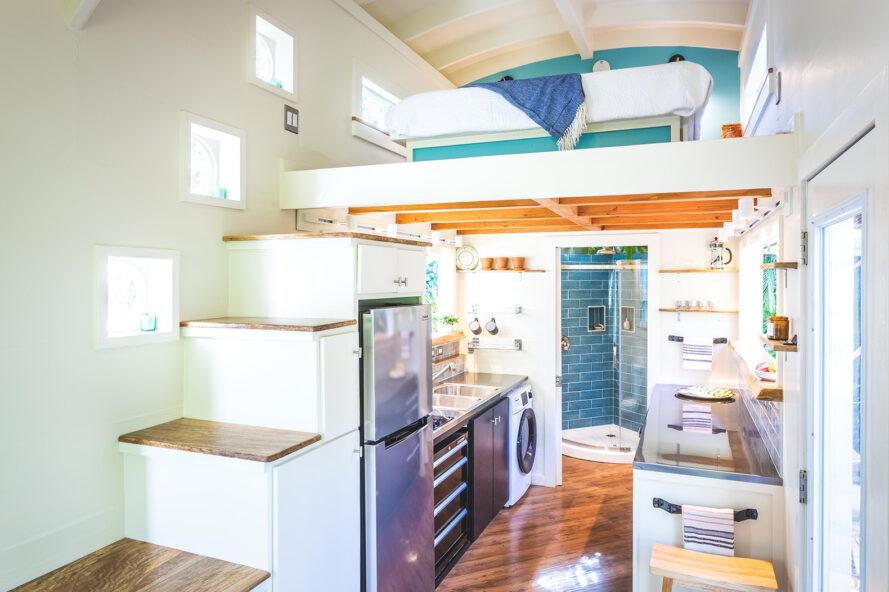 Various windows of different shapes and sizes are strategically scattered in different areas of this tiny house
