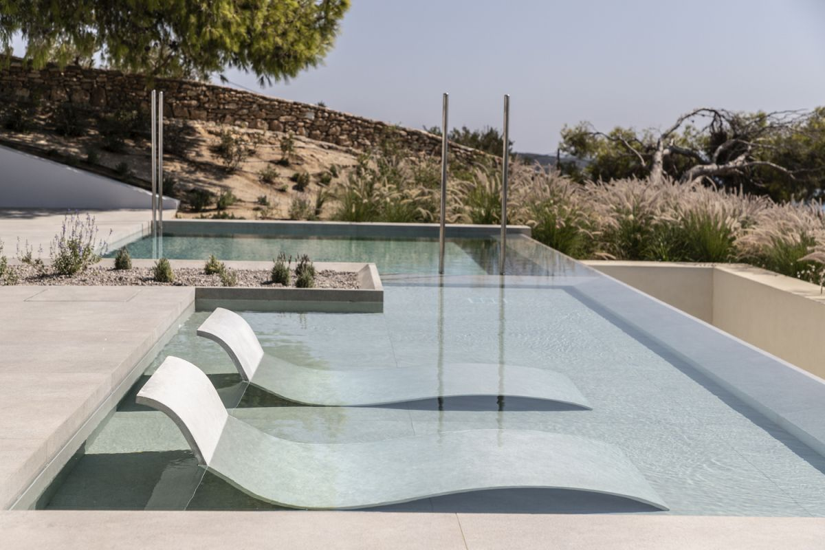 A shallow pond with lounge chairs is one of several outdoor features that make this house amazing