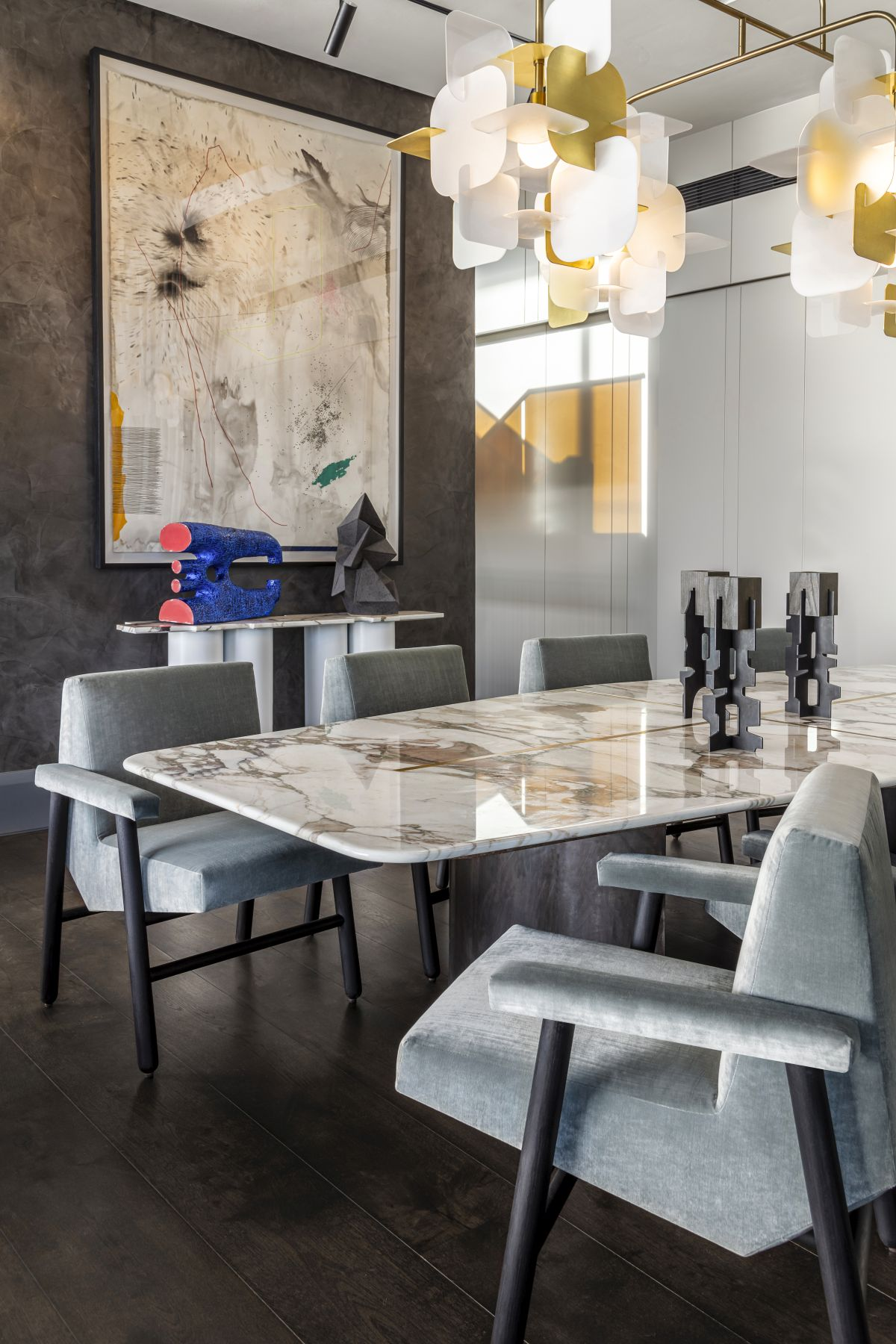 A contemporary chandelier adds visual interest to the already stylish dining area
