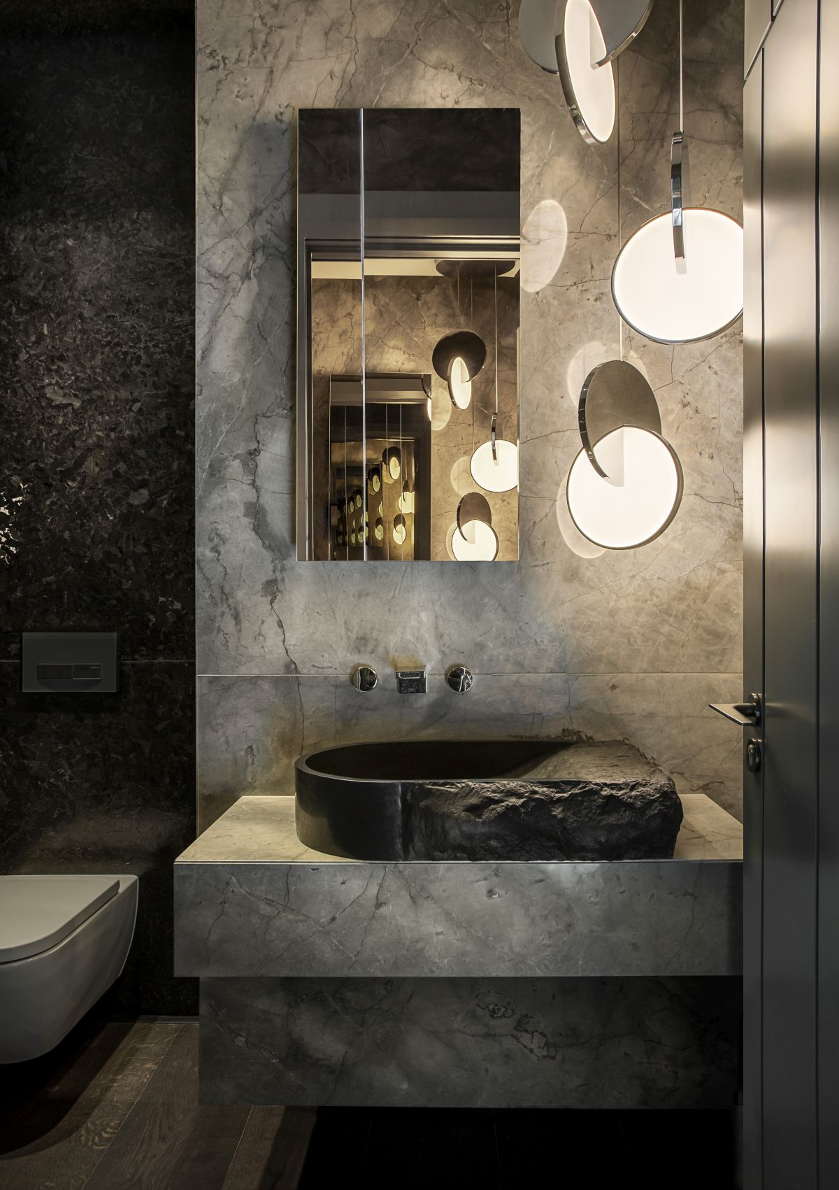 A sculptural washbasin and a set of cascading pendant lamps give this bathroom a very sophisticated look