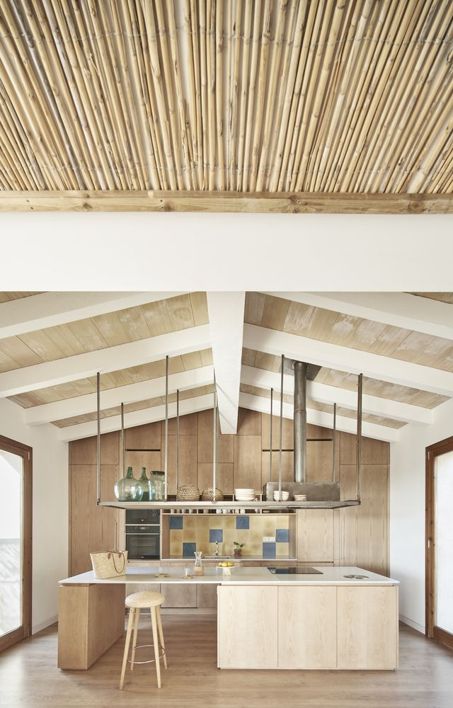 the kitchen has hanging ceiling storage and a simple and airy design