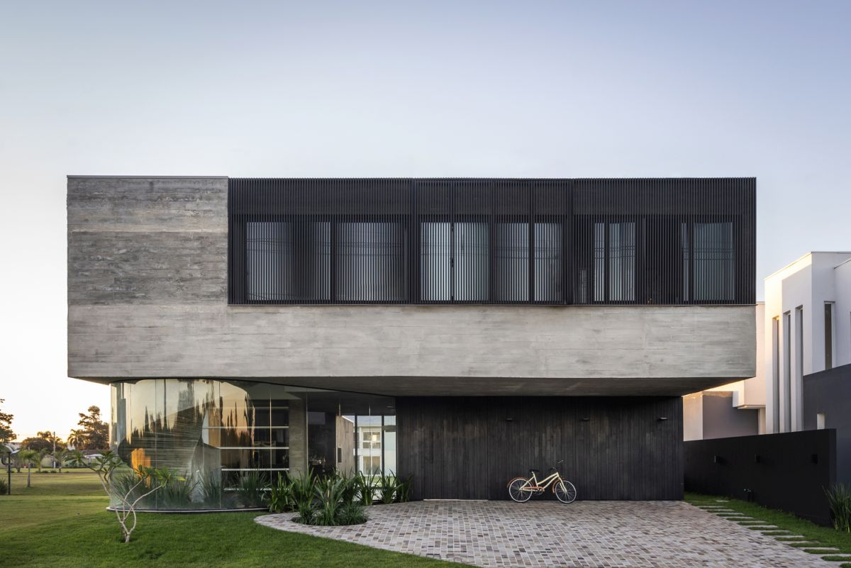 The exterior of the house is a simple and elegant combination of exposed concrete and black wood