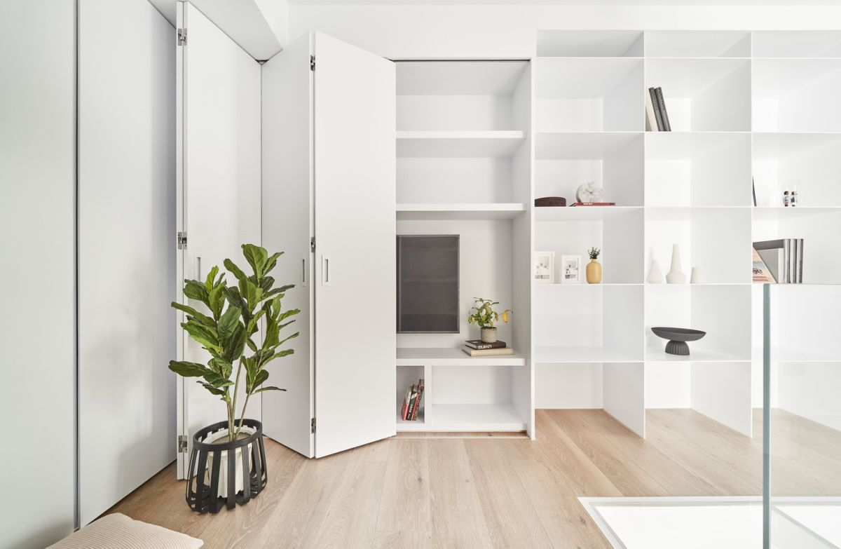 Folding doors reveal ample storage inside the custom-designed wall units