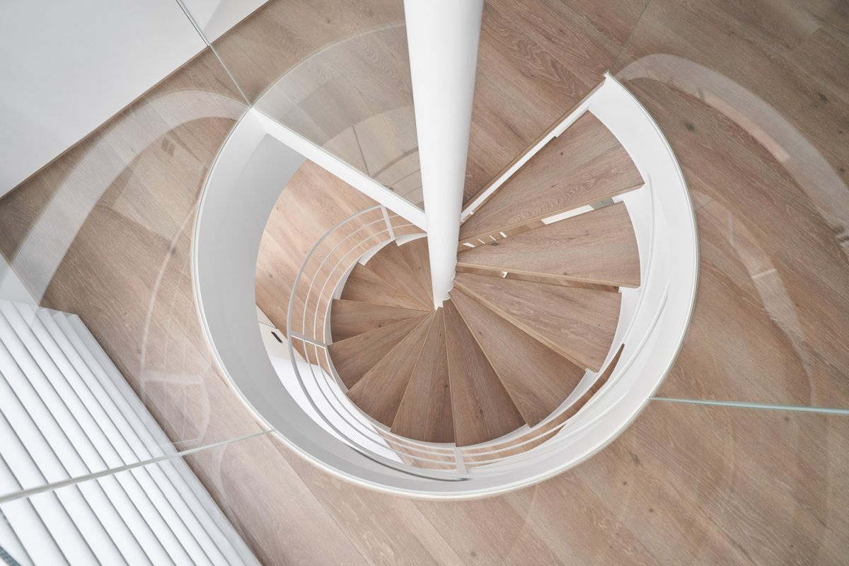 The wooden stairs appear to float around the central white pole, giving the staircase a sophisticated look