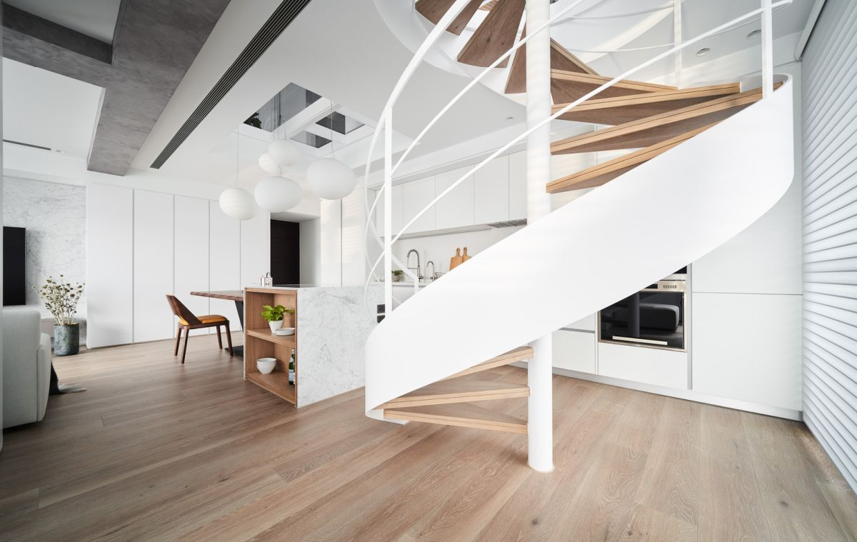 The spiral staircase which connects the two floors is part of the open kitchen's layout