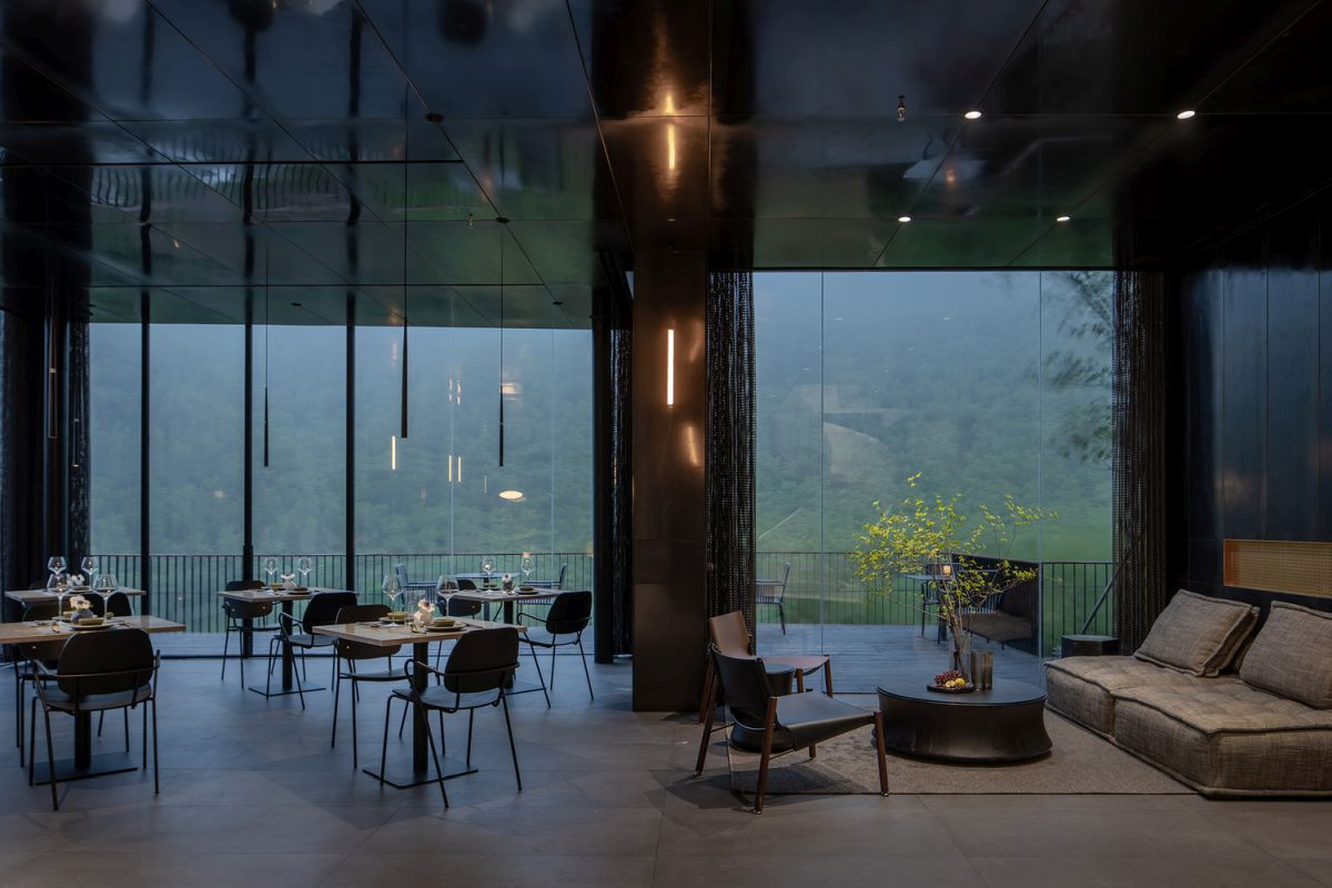 The common areas have full-height transparent glass windows which expose them to the lush landscape