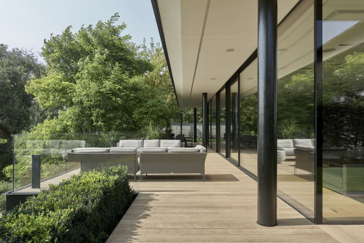 Transparent glass railings frame the outdoor spaces and ensure an unobstructed view towards the river