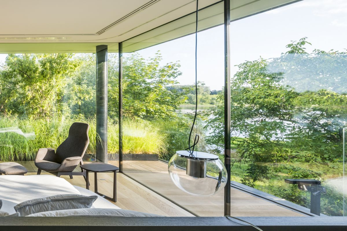Large floor-to-ceiling windows and glass walls reveal the magnificent view of the river area