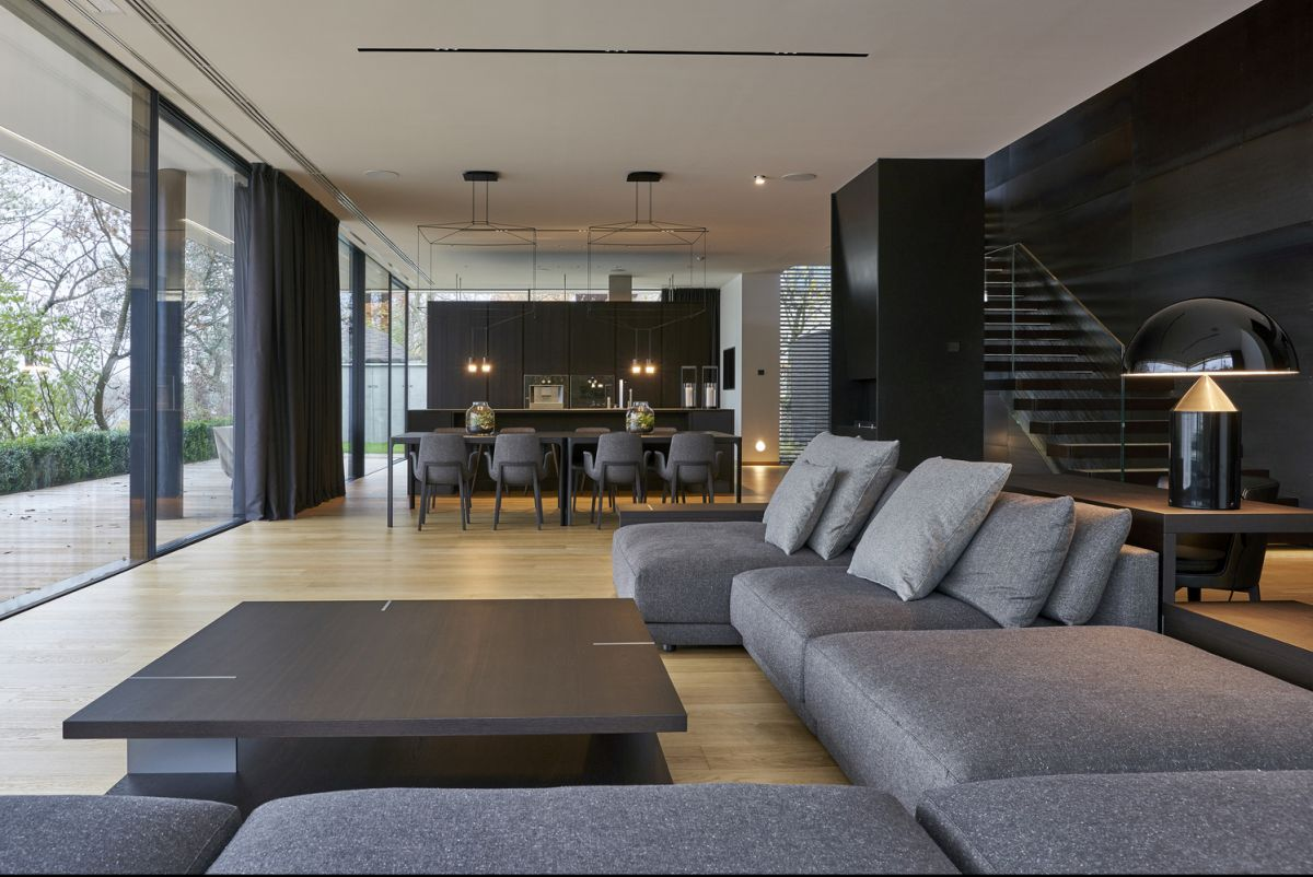 The black staircase is beautifully integrated into the decor, featuring a black wall backdrop and glass railings