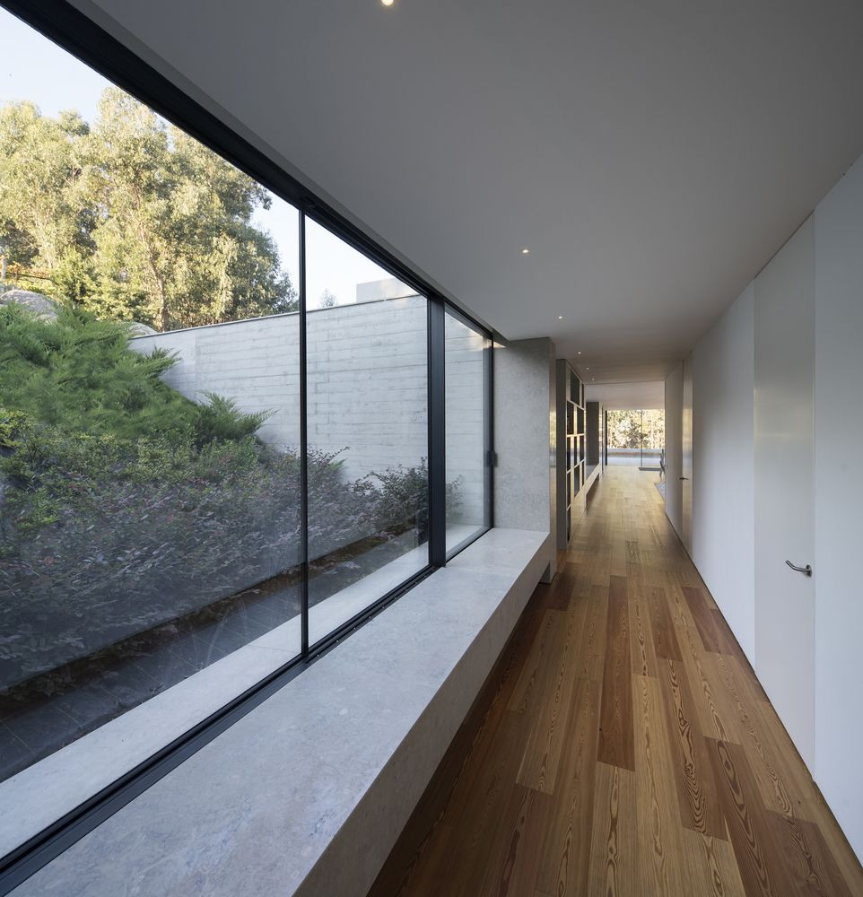 Large windows frame close views of the sloping terrain, allowing the land to become a part of the interior design