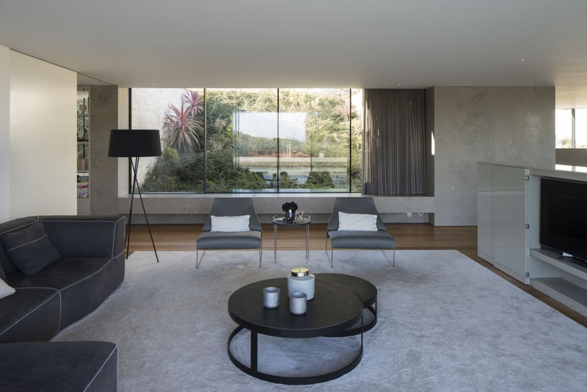 Large windows allow the sloping terrain to create a beautiful green backdrop for the living areas