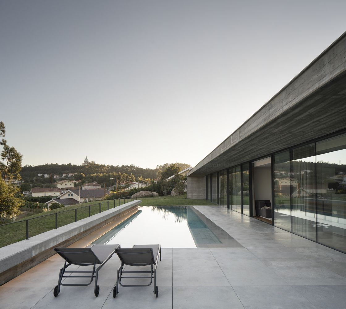 The lower section of the house extends down the slope and looks onto a big open terrace with a built-in swimming pool
