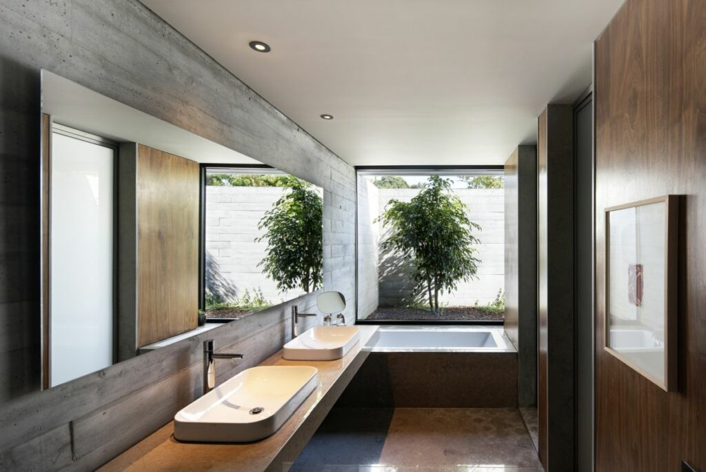 Natural stone and wood in combination with the garden view give the master bathroom a spa-inspired look