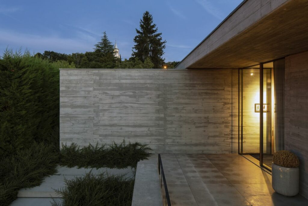 The entrance is reached via a set of stone stairs that go up the slope on the side of the house