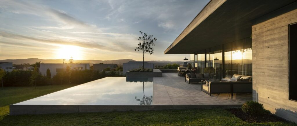 The backyard patio seamlessly transitions into an infinity edge pool