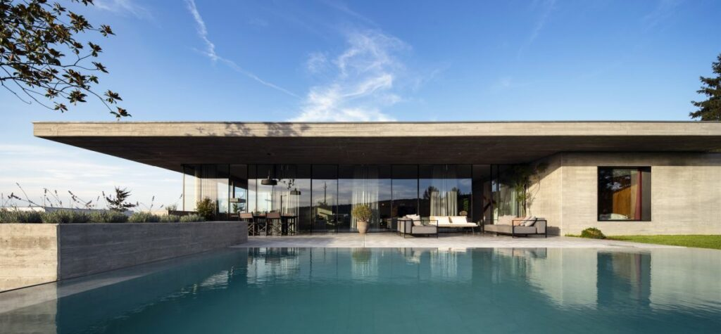 A large infinite edge swimming pool occupies a big section of the backyard
