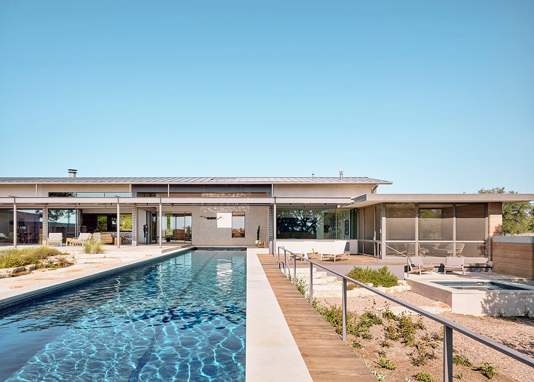 The sparse vegetation and overall landscape complement the house and its simple design