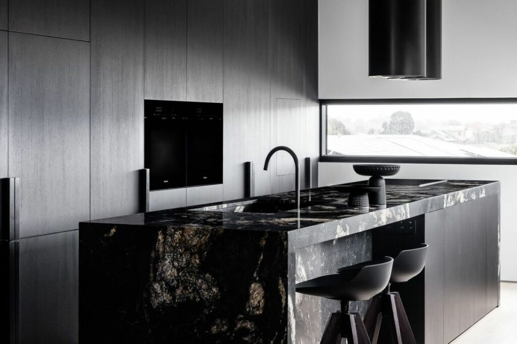 The focal point of the kitchen is a large island made of dark granite