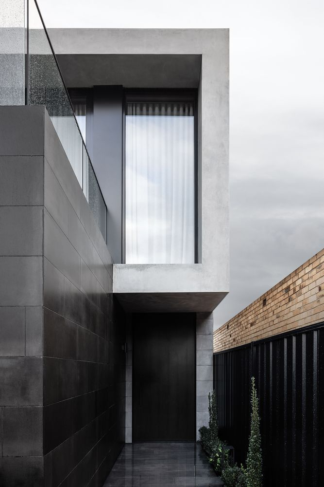 The entrance is framed by a black accent wall and a fence which contrast with the light gray exterior walls