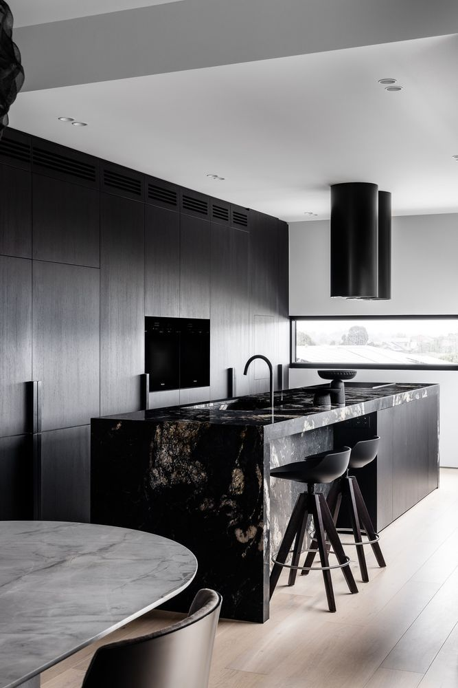 The kitchen features a black and gold color palette which gives it a very sophisticated look