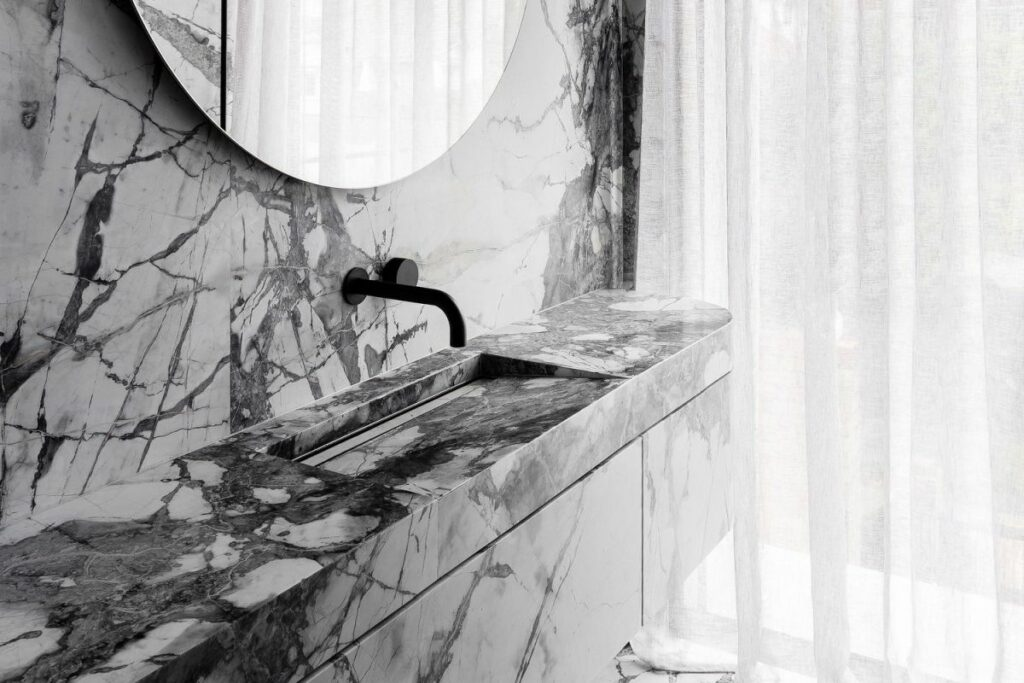 White marble with rich veins was used for the walls, floor and vanity of this exquisite powder room