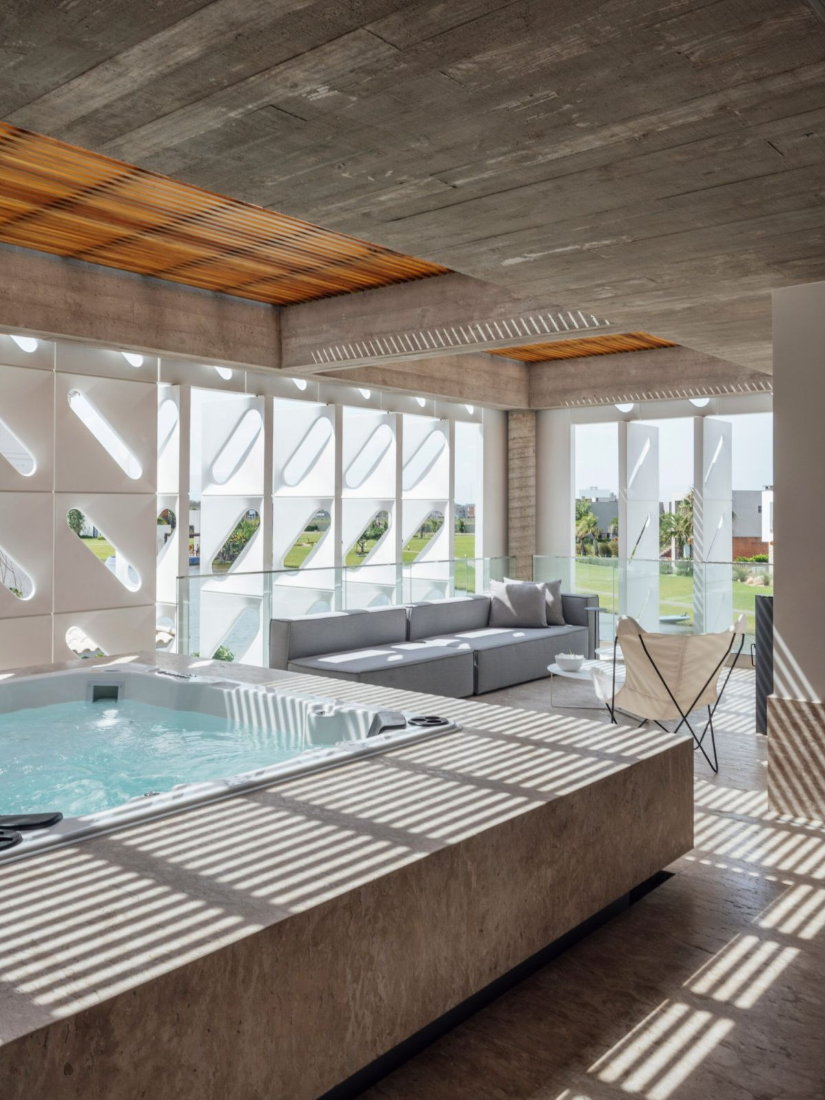 On the upper floor there's a covered terrace with a hot tub concealed behind the pivoting shutters
