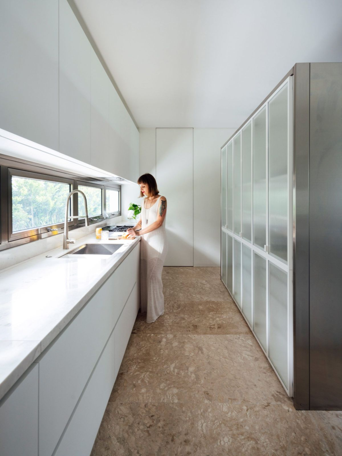 The kitchen is all white with metal accents and an earthy brown floor