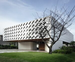 Modern White House With Perforated Shutters Across Its Facade