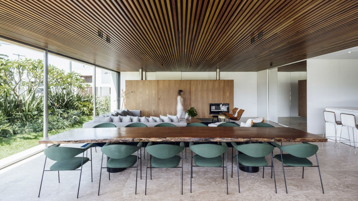 The living room and dining area have a panoramic view of the lush garden