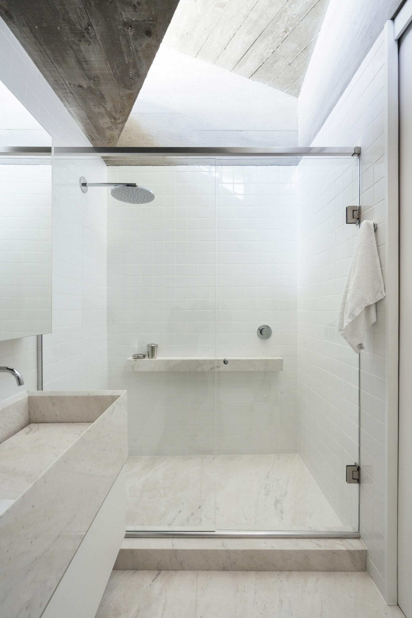 The bathrooms have bright and subdued designs with elegant marble accents and glass partitions