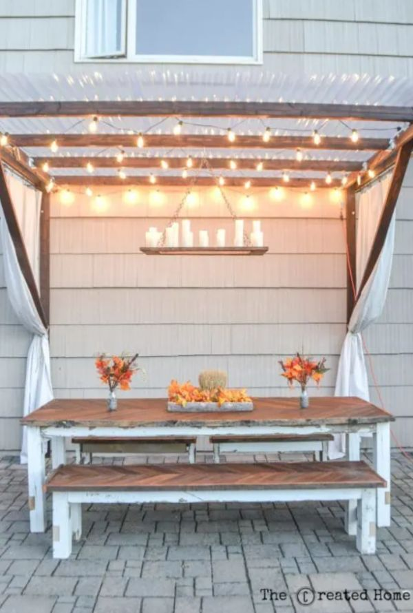 A pergola with curtains and string lights
